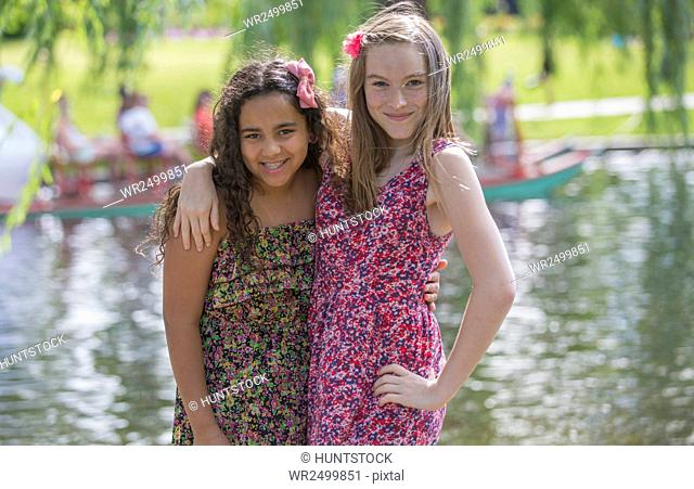 Portrait of two Hispanic teen sisters posing together in a park