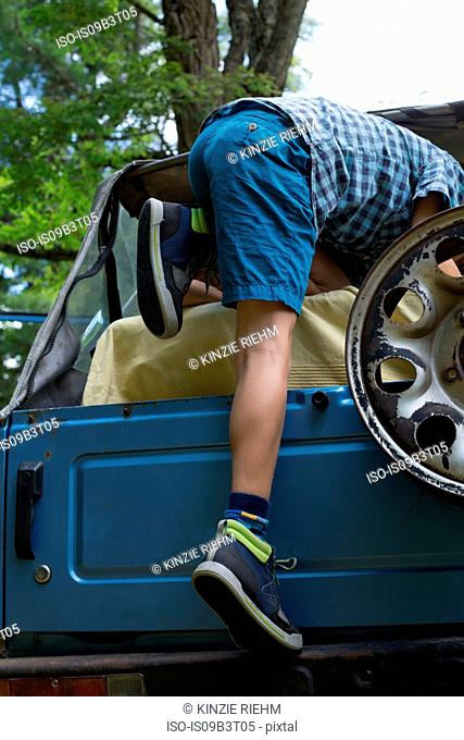 Young boy climbing into off road vehicle