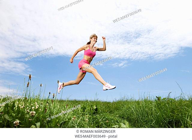 Germany, Bavaria, Young woman running on grass
