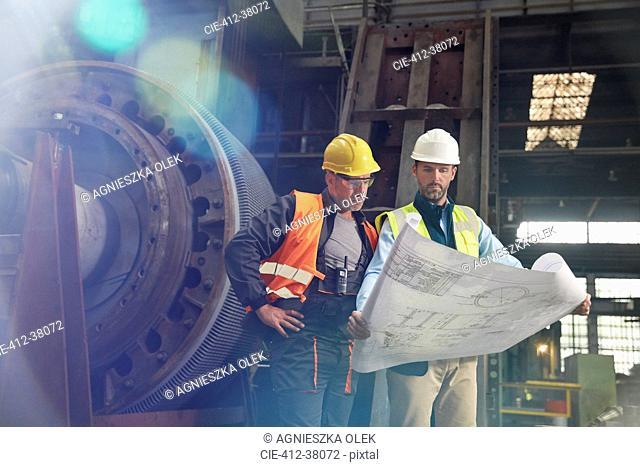 Engineers reviewing blueprints in steel factory