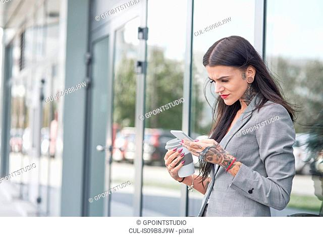 Businesswoman outdoors, holding coffee cup and smartphone, tattoos on hands