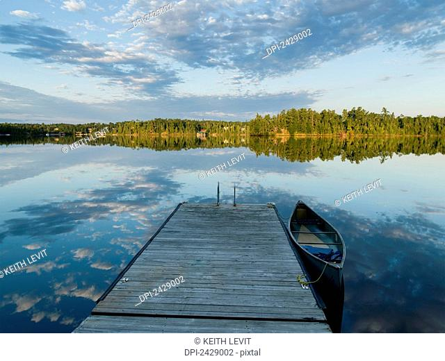 A canoe tied to a wooden dock and clouds reflected in a tranquil lake; Ontario, Canada