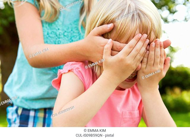 Cropped shot of girl with hands covering friend's eyes in garden