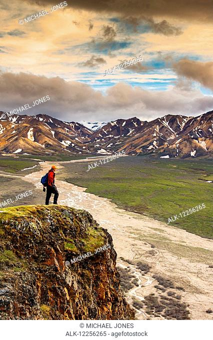 A man standing on a bluff at Polychome Pass with the Plains of Murie and the Alaska Range in the background, Denali National Park, Interior Alaska