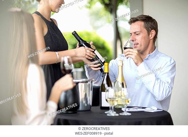 Man in restaurant tasting red wine