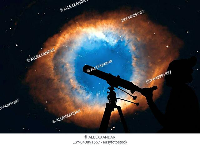 Girl looking at the stars with telescope. The Helix Nebula or NGC 7293 in the constellation Aquarius. Elements of this image are furnished by NASA