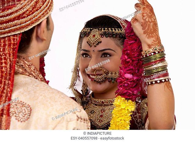 Gujarati bride putting a garland on a groom