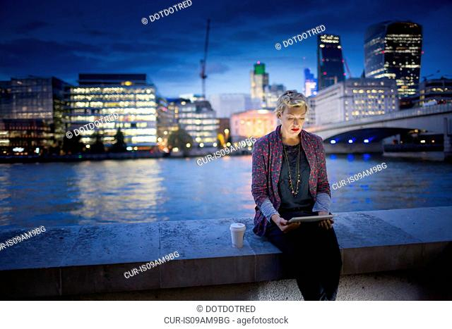 Mature businesswoman sitting on Thames waterfront using digital tablet at night, London, UK