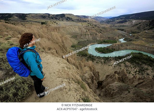 Female hiker with backpack looking down on the Chilcotin River, Cariboo Chilcotin region, British Columbia, Canada