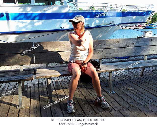 A woman tourist in tee-sirt and short pants sits on a wood bench on a pier for a cruise ship at Tobermory, Ontario