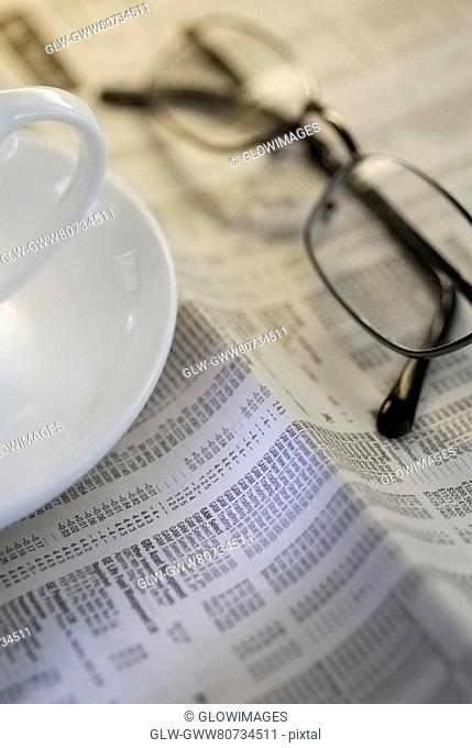 Close-up of a tea cup and eyeglasses on a newspaper