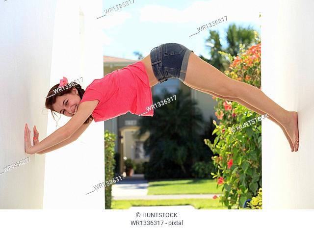 Young woman stretching between two walls and smiling