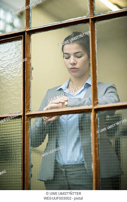 Young businesswoman checking the time