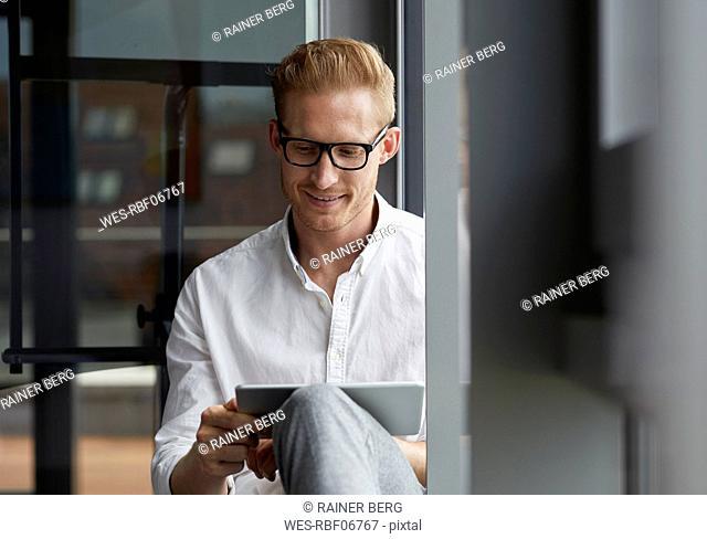 Smiling businessman sitting on windowsill using tablet