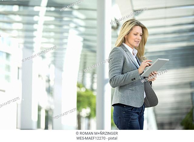 Businesswoman using tablet outdoors