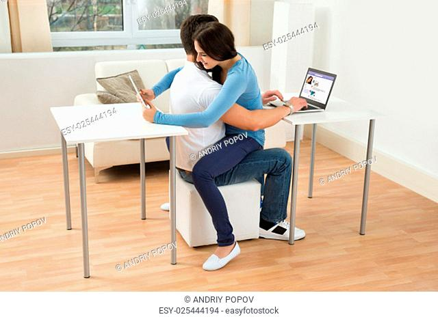 Portrait Of A Young Couple At Home Using Digital Tablet And Laptop