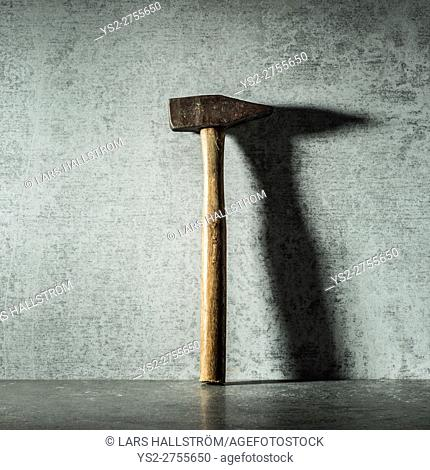Vintage hammer and shadow on stone wall. Still life of work tool. Concept of diy and repair