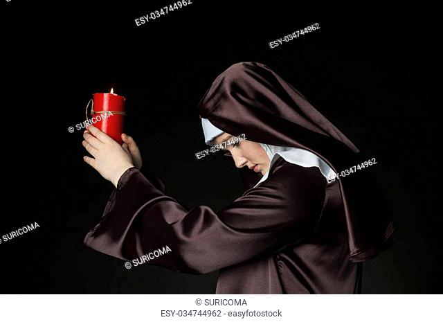 Young catholic nun is holding candle in her hands. Photo on black background. Side view