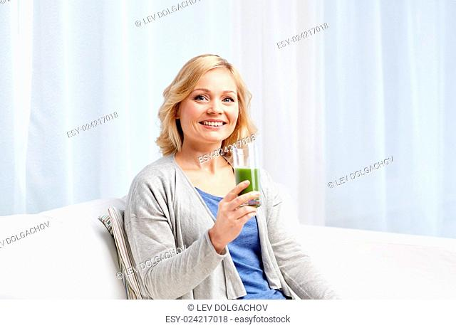 healthy eating, vegetarian food, dieting, detox and people concept - smiling middle aged woman drinking green fresh vegetable juice or smoothie from glass at...