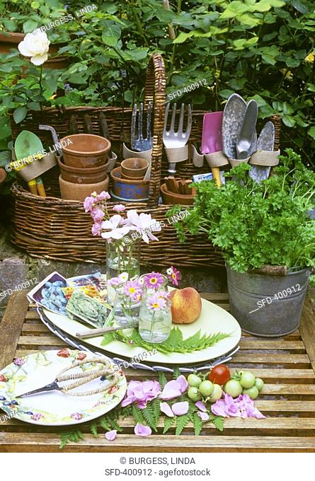 A basket of garden tools, flowers and herbs