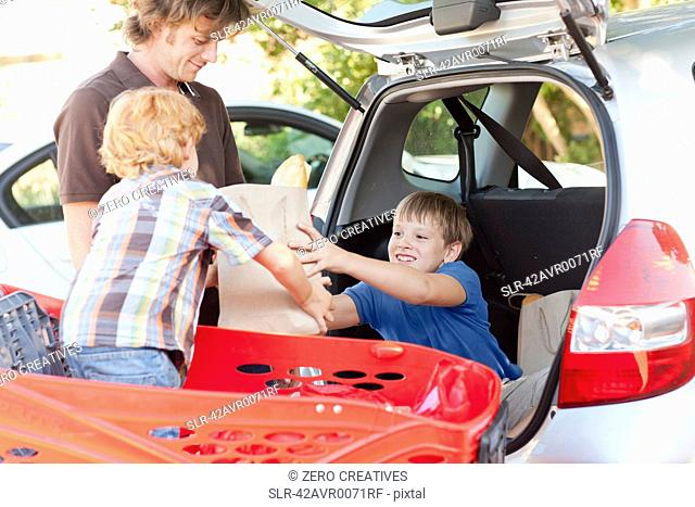 Father and sons unloading groceries