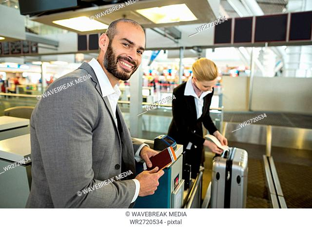 Smiling businessman standing with passport while attendant sticking tag to luggage