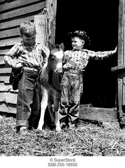 Two cowboys standing with a foal in front a stable