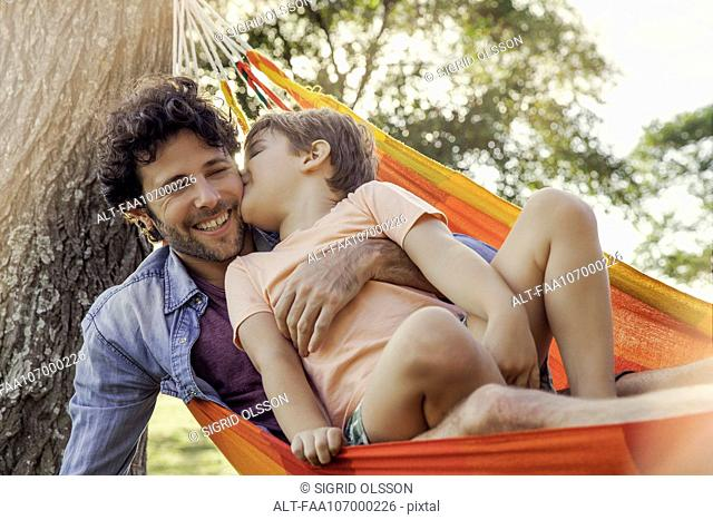 Father and son relaxing together in hammock