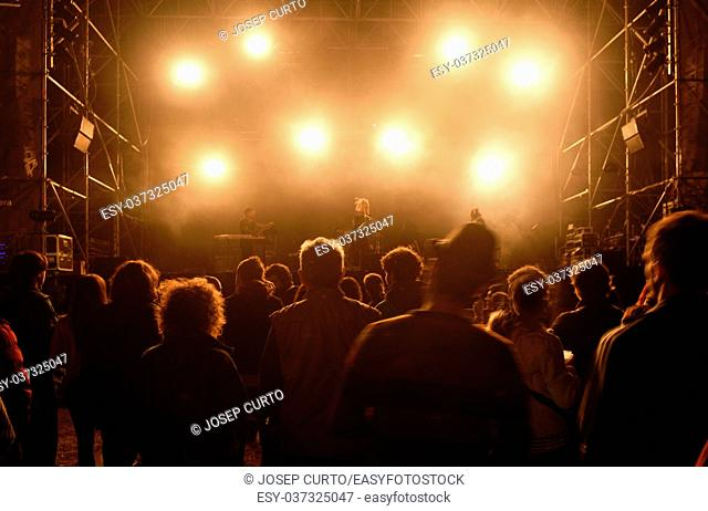 People silhouettes in front of bright stage lights, music