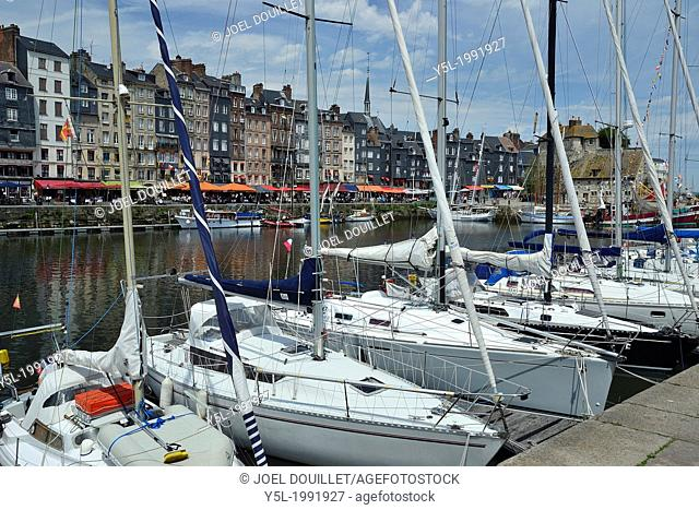 Sailing boats in the old port (Vieux Bassin) and tourists at pavement cafes. Sidewalk restaurants along the quay of the Honfleur harbour