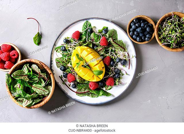 Green vegan salad with berries strawberry, blueberry, sprouts, young beetroot leaves, mango on plate. Ingredients in wooden bowls above over grey concrete...