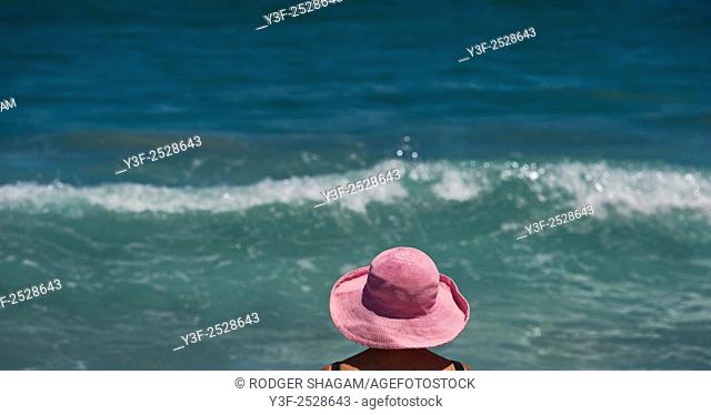 A woman in a pink sun hat,stands at the seaside, Cape Town, South Africa