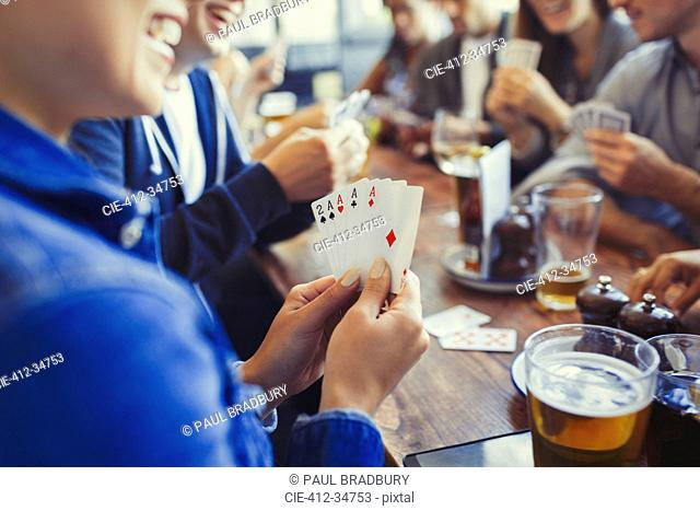 Woman holding aces four of a kind, playing poker and drinking beer with friends at table in bar
