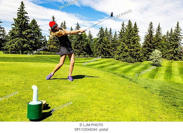 A female golfer driving a golf ball down the green grass of a golf course with her driver and ball in mid-air; Edmonton, Alberta, Canada