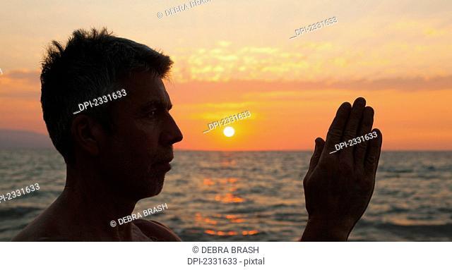 A man in prayer or yoga pose as the sun set on a tropical beach;Puerto vallarta mexico