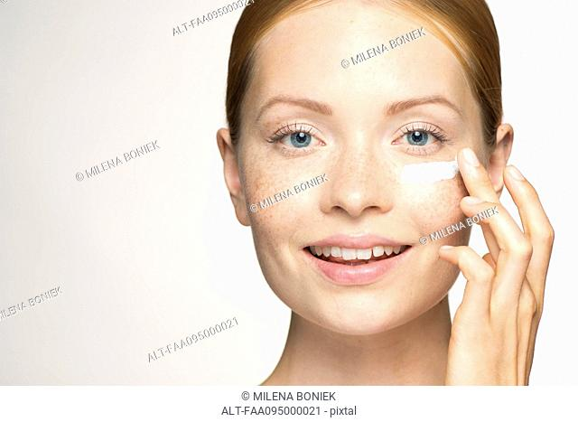 Young woman applying moisturizer under eye