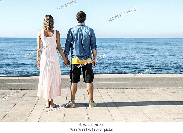 Spain, Mid adult couple standing at Atlantic Ocean, looking at view