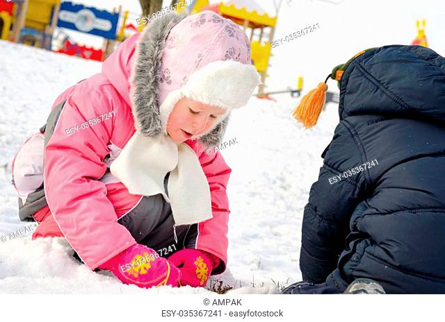 Adorable little girl in a trendy pink winter outfit bending down gathering snowballs in the snow