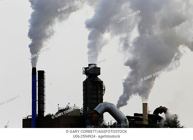 Air pollution coming from smoke stacks at a paper mill