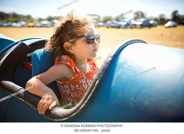 Girl sitting in barrel cart, wearing sunglasses looking away