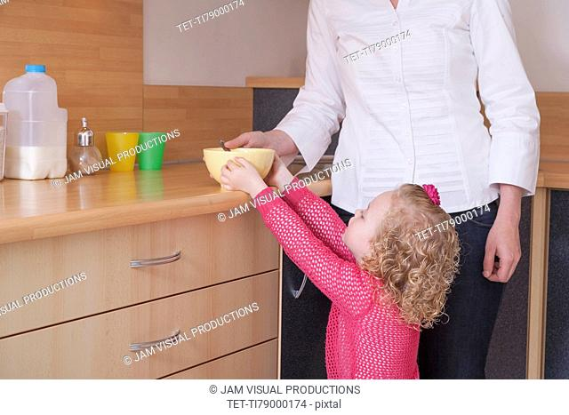 Mother helping daughter (4-5) take bowl from kitchen counter
