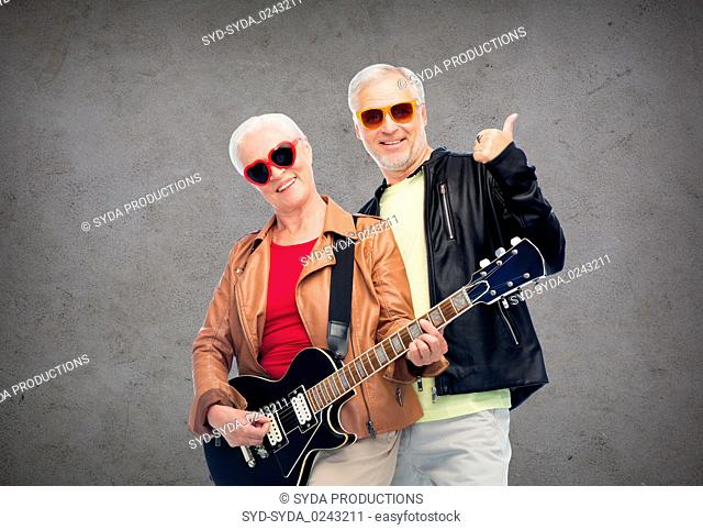 happy senior couple with guitar showing thumbs up