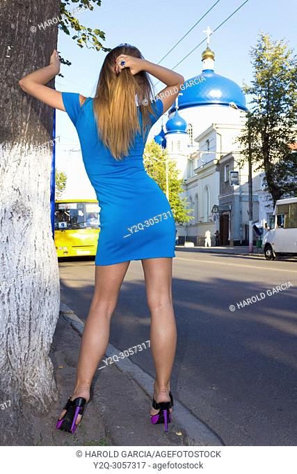 Beautiful, attractive Ukrainian woman wearing a blue dress reclining to a tree posing near the Orthodox St Michael's cathedral for a photographic sequence in...