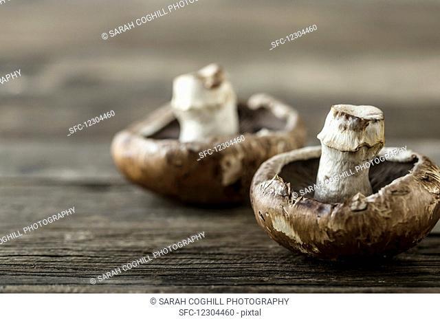 Two portobello mushrooms on a wooden surface