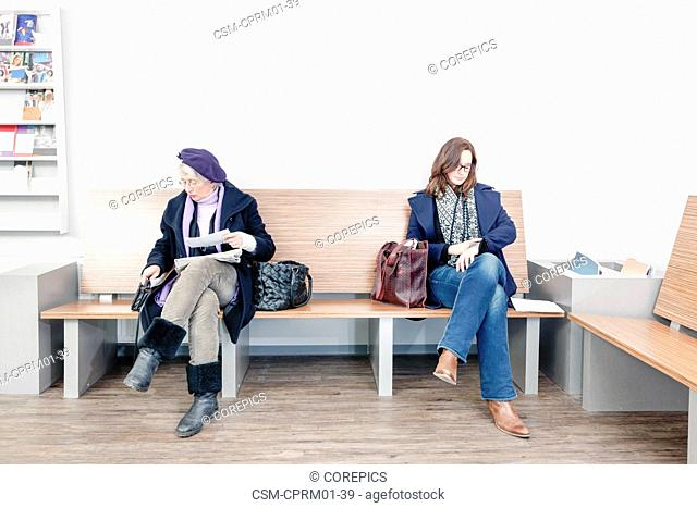 Two women waiting impatiently in the waiting room of a medical practice