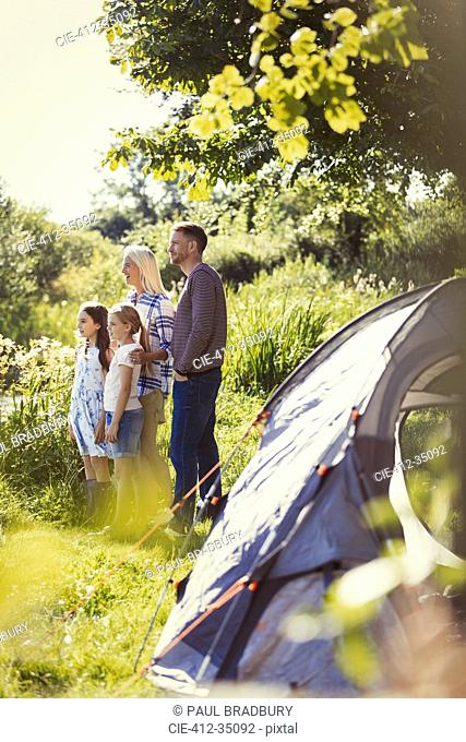 Family standing at sunny campsite tent