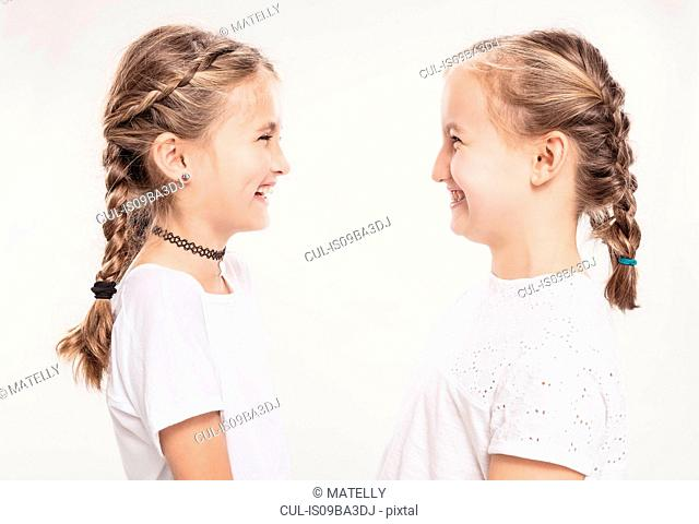Studio portrait of two girls with hair plaits face to face, head and shoulders
