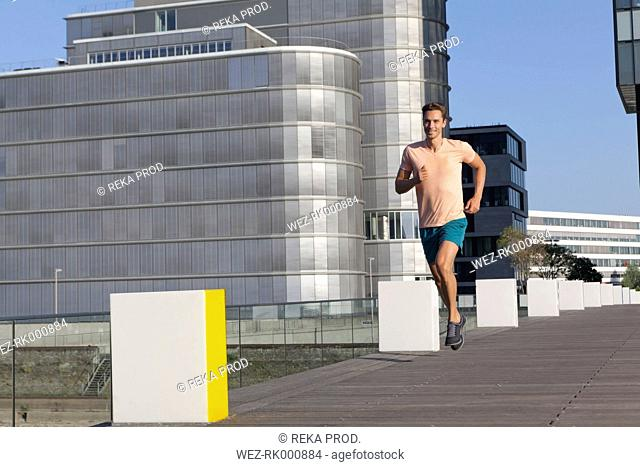 Germany, North Rhine Westphalia, Duesseldorf, Mid adult man jogging over bridge