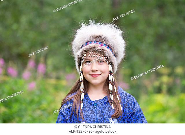 A young Inupiat tween girl in a traditional Eskimo Kuspuk and native headdress, Hatcher Pass, Palmer, Southcentral, Summer