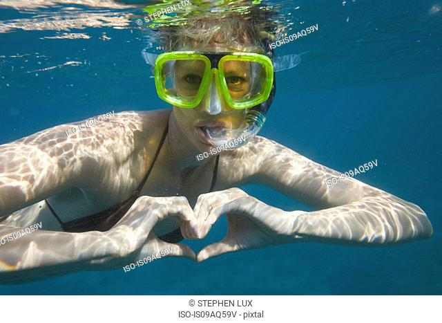 Portrait of female snorkeler making heart shape with hands, Bali, Indonesia